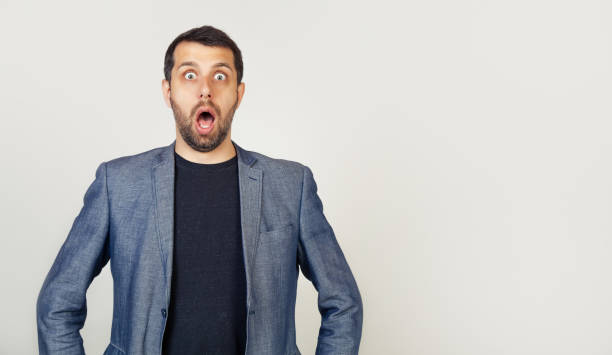 A man with a beard opened his mouth, scared and shocked by an expression stock photo