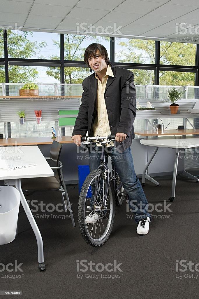 Homem com uma bicicleta em Escritório foto de stock royalty-free