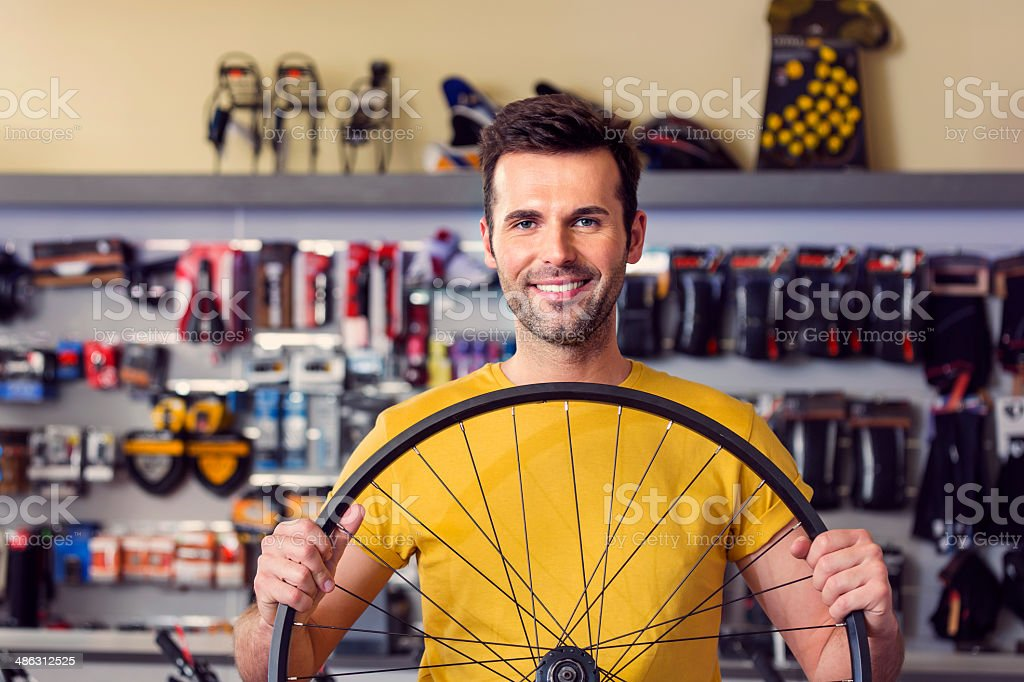 Man with a bicycle wheel Portrait of sales clerk in a sports store, holding a bicycle wheel and smiling at camera. 30-34 Years Stock Photo
