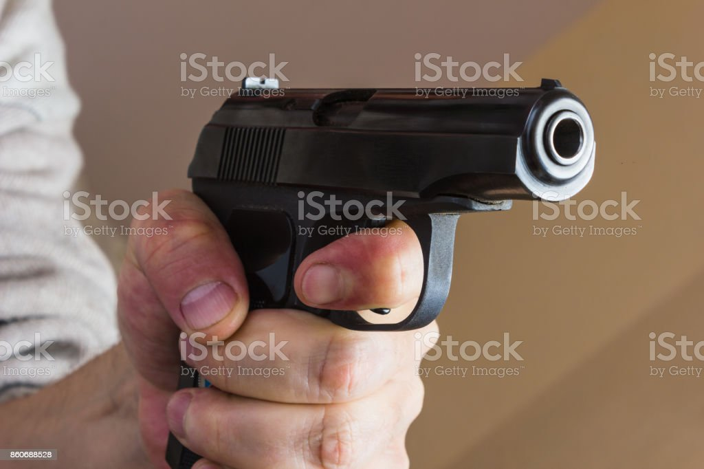 man with a black gun in his hand stock photo