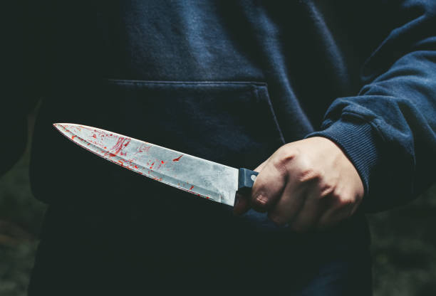 A man with a bloody knife in his hand stock photo