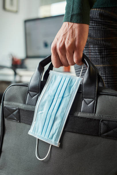 man with a briefcase and a surgical mask stock photo