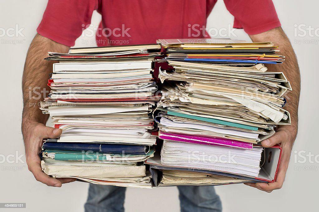 Man with a bunch of old newspapers in the hands stock photo