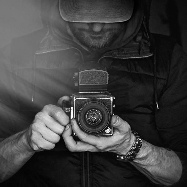 ein mann mit einer kamera. schwarz / weiß fotografie - modedetails stock-fotos und bilder