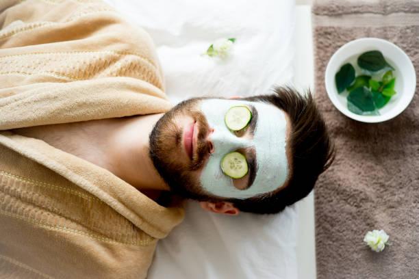 hombre con una máscara de arcilla - cuidado del cuerpo fotografías e imágenes de stock
