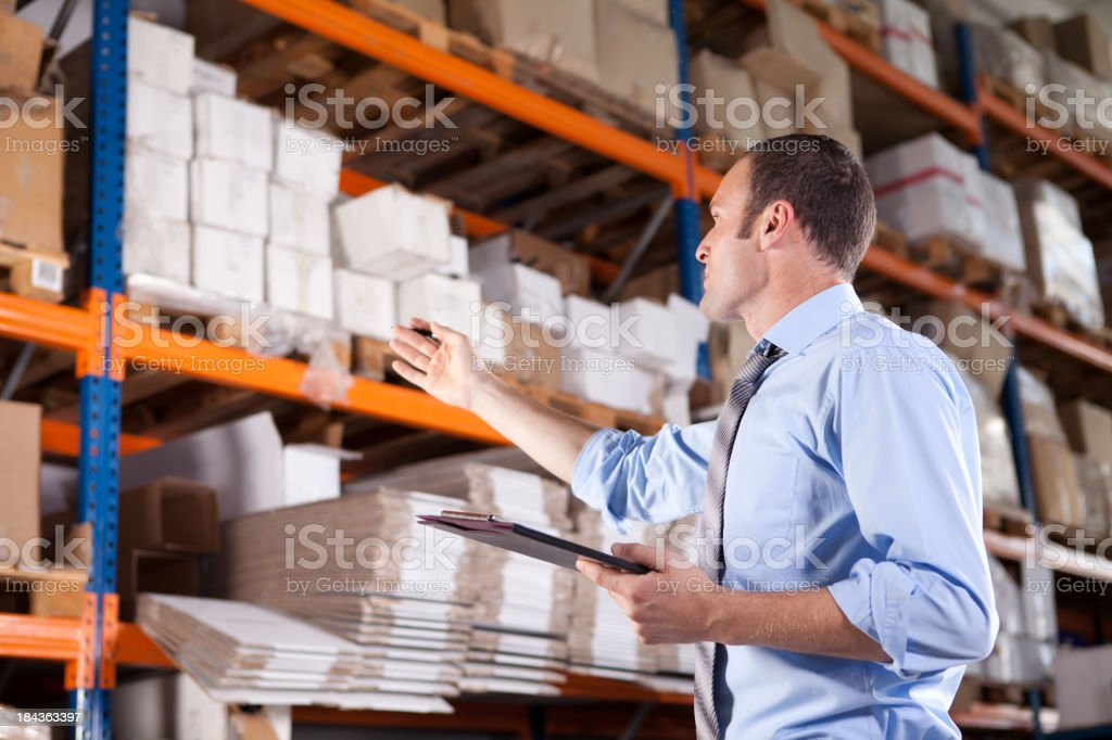 Man with a clipboard and pen in a warehouse stock photo