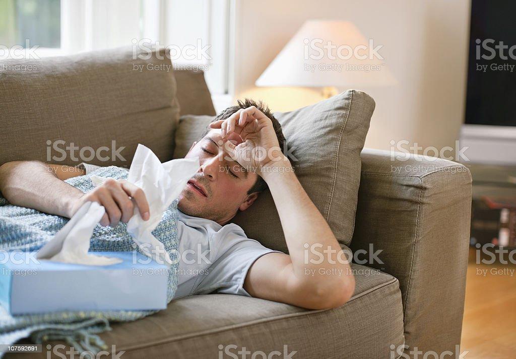 Mann mit einem kalten Entspannung in sofa hält das Gewebe – Foto