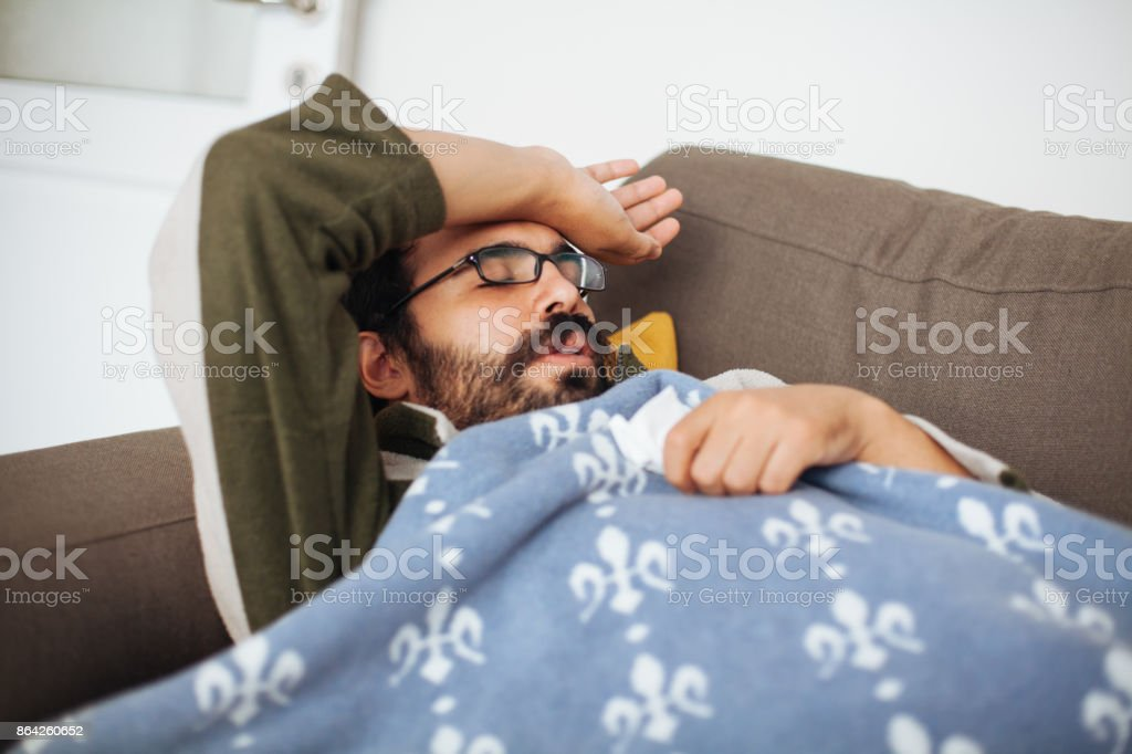 Man with a cold lying in sofa holding tissues royalty-free stock photo