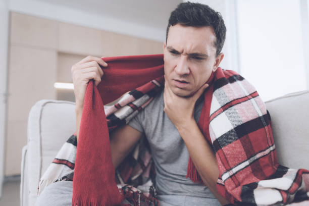 a man with a cold sits on the couch, hiding behind a red rug. he has a sore throat - infezione respiratoria foto e immagini stock
