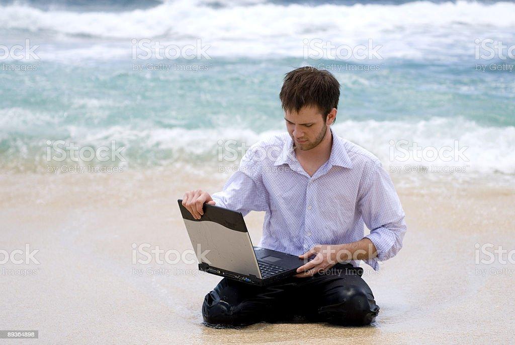 Człowiek z komputerem na plaży zbiór zdjęć royalty-free