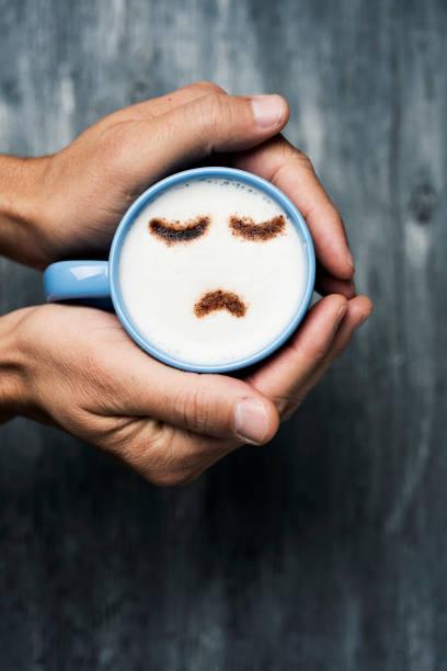 uomo con una tazza di cappuccino con un viso triste - blue monday foto e immagini stock