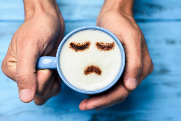 mann mit einer tasse cappuccino mit einem traurigen gesicht - depression stock-fotos und bilder