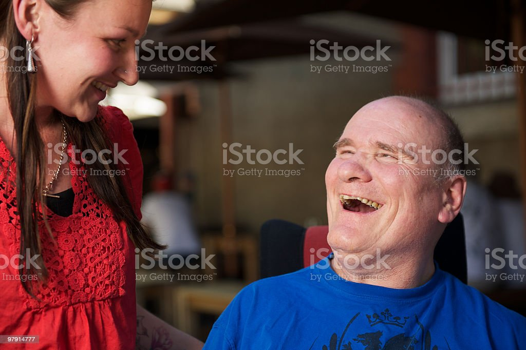 Man with a disability laughing to woman at cafe royalty-free stock photo