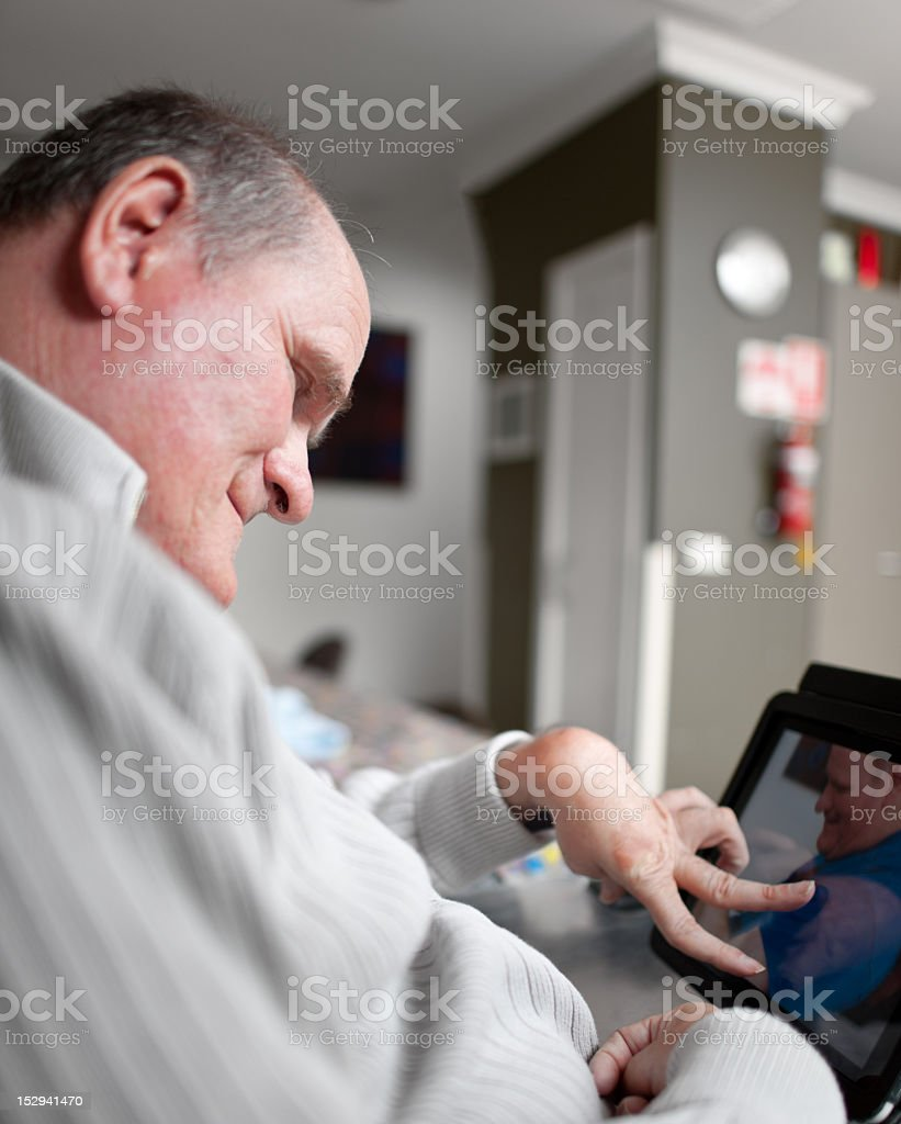 Man with a disability looks at photos on computer stock photo