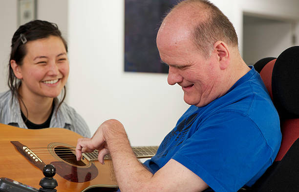 Man with a Disability playing Guitar One of many portraits of  people with an intellectual disability available on my website  persons with disabilities stock pictures, royalty-free photos & images