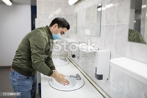 Concept, diseases, viruses, allergies, air pollution. Portrait of a young man wearing a protective mask and washing his hands in a public bathroom. The face of a young man wearing a mask to prevent germs, toxic fumes and dust. Prevention of bacterial infection with Corone virus or Covid 19 in the air around streets and gardens.