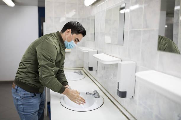 L'homme avec un masque de visage lave ses mains dans une salle de bains publique - Photo