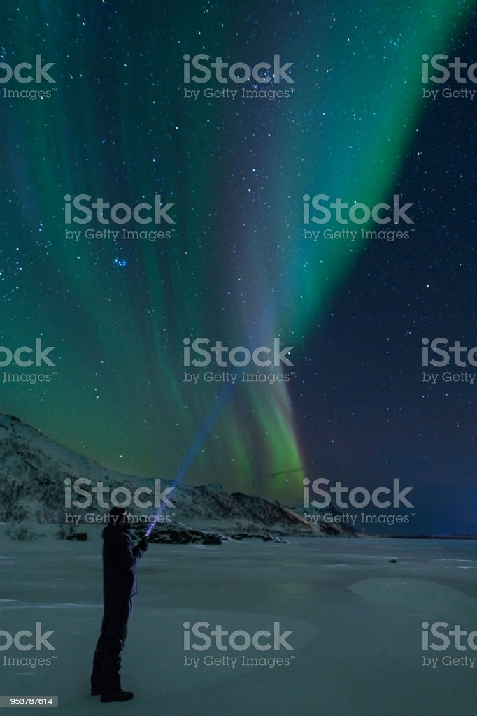 Man with a flashlight looking at Northern Lights, Aurora Borealis over the Lofoten - foto stock