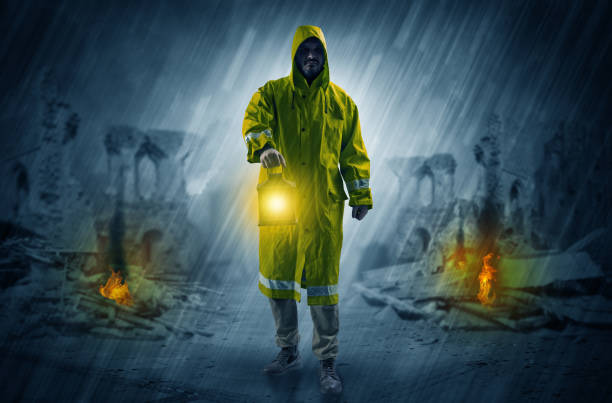 Man with a glowing lantern at a catastrophe scene Destroyed place after a catastrophe with man in raincoat and lantern concept bootes stock pictures, royalty-free photos & images