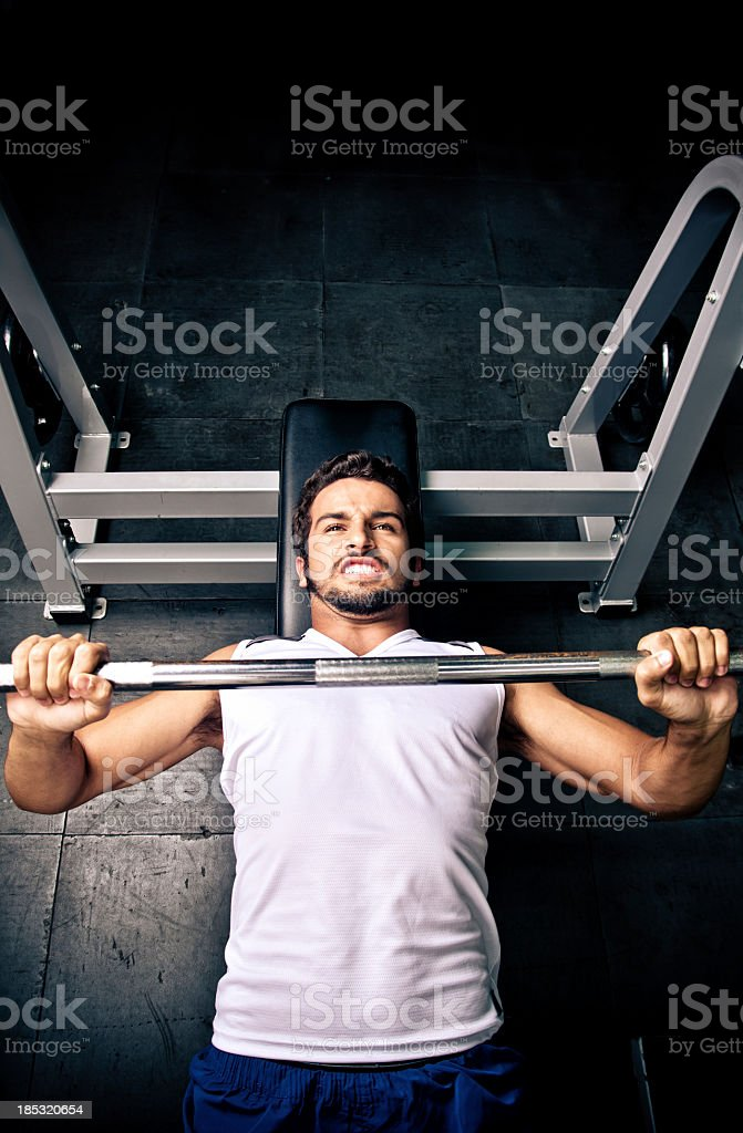 A man with a gray cutoff bench pressing stock photo
