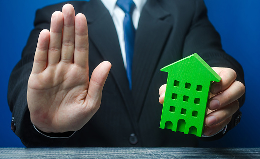 Man with a green house makes a stop gesture. Bank refusal to provide a mortgage loan. Housing problems, unscrupulous dishonest company builder. Confiscation pledged property. Refusal residence permit.