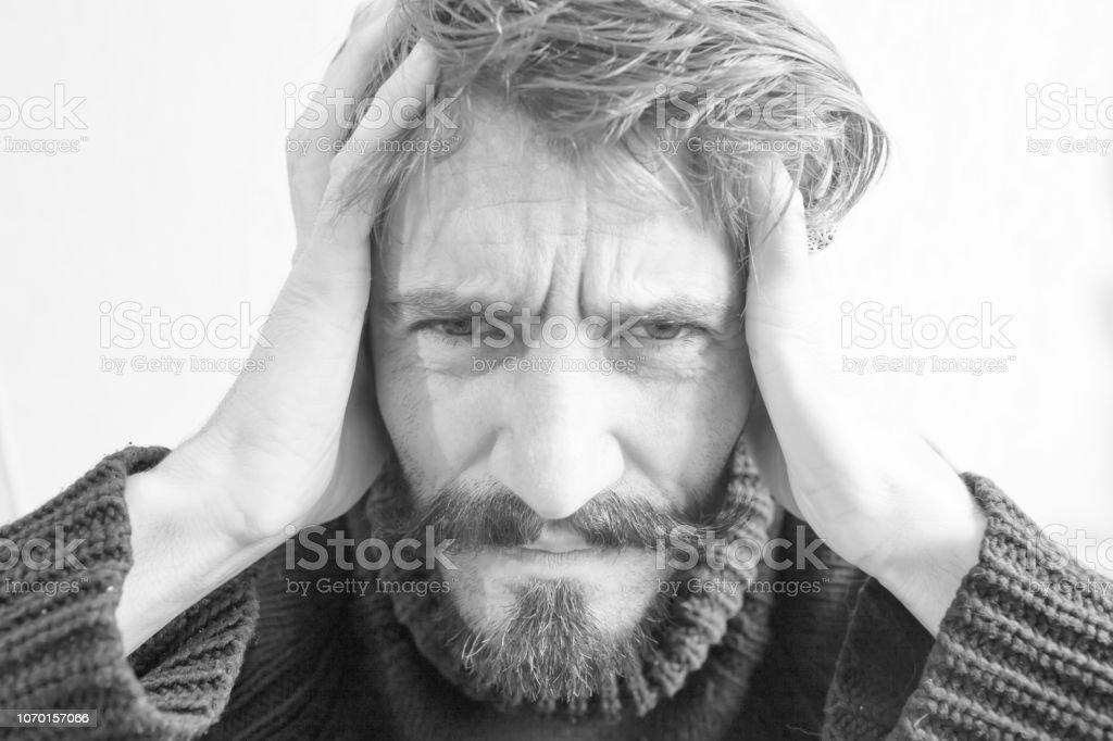 Un hombre con una mueca de dolor aprieta su cabeza con sus manos - foto de stock