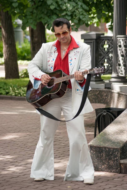 man with a guitar in the costume of elvis presley - elvis stock photos and pictures