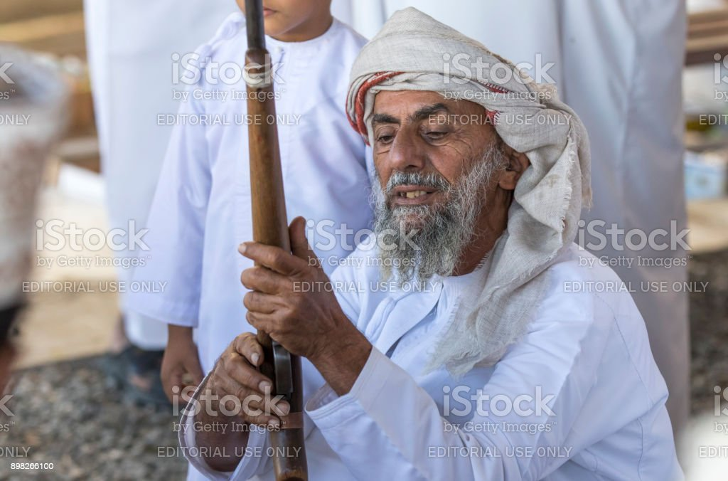 man with a gun at a market stock photo