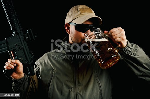 istock man with a gun drinking beer 649634238