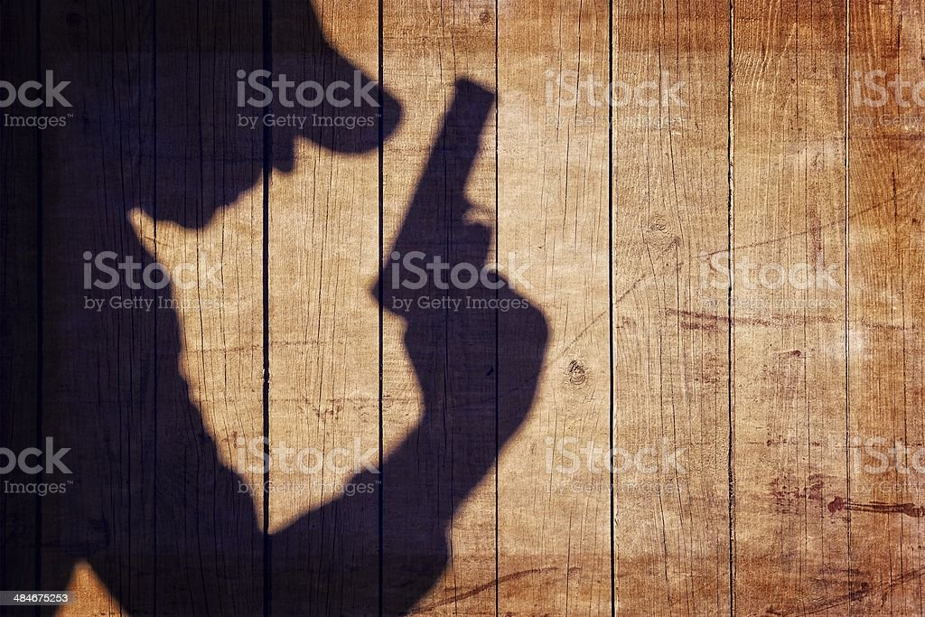 Man with a gun in shadow on a wooden background stock photo