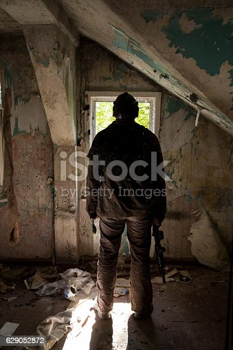 istock man with a gun in the Abandoned destroyed house 629052872