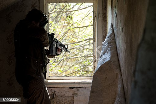 istock man with a gun in the Abandoned destroyed house 629053004