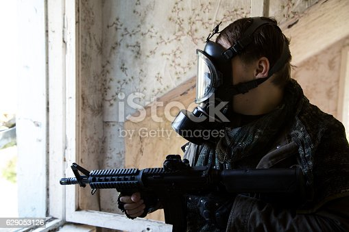 istock man with a gun in the Abandoned destroyed house 629053126