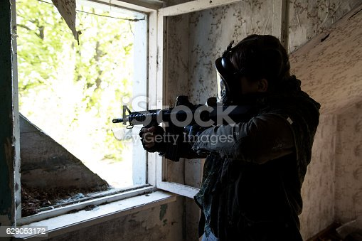 istock man with a gun in the Abandoned destroyed house 629053172