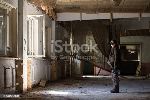 istock man with a gun in the Abandoned destroyed house 629053368