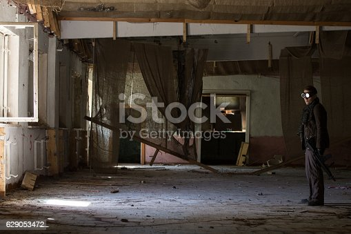 istock man with a gun in the Abandoned destroyed house 629053472