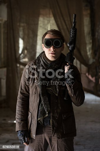 istock man with a gun in the Abandoned destroyed house 629053518