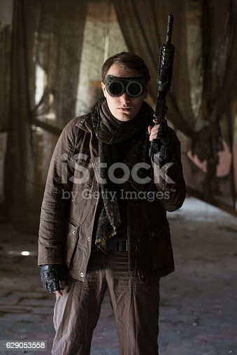 istock man with a gun in the Abandoned destroyed house 629053558