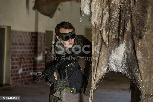 istock man with a gun in the Abandoned destroyed house 629053674