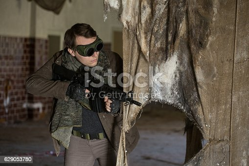 istock man with a gun in the Abandoned destroyed house 629053780