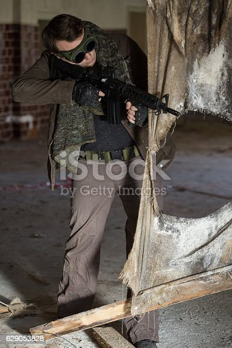istock man with a gun in the Abandoned destroyed house 629053828