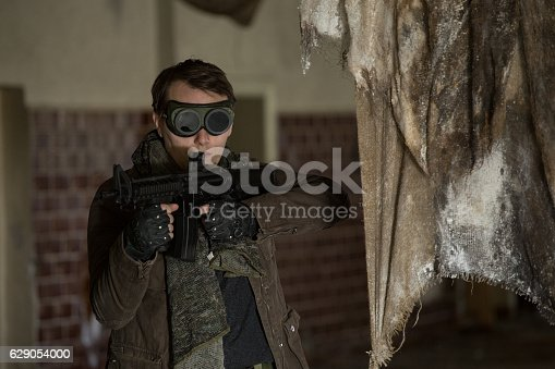 istock man with a gun in the Abandoned destroyed house 629054000