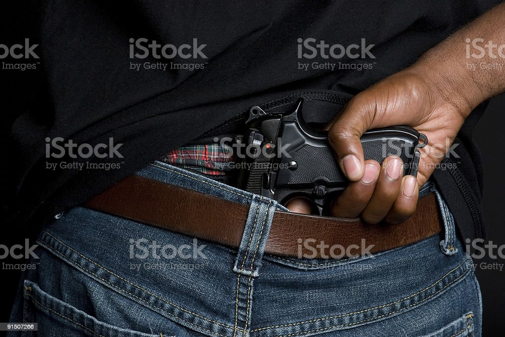 A man with a gun tucked into his pants stock photo