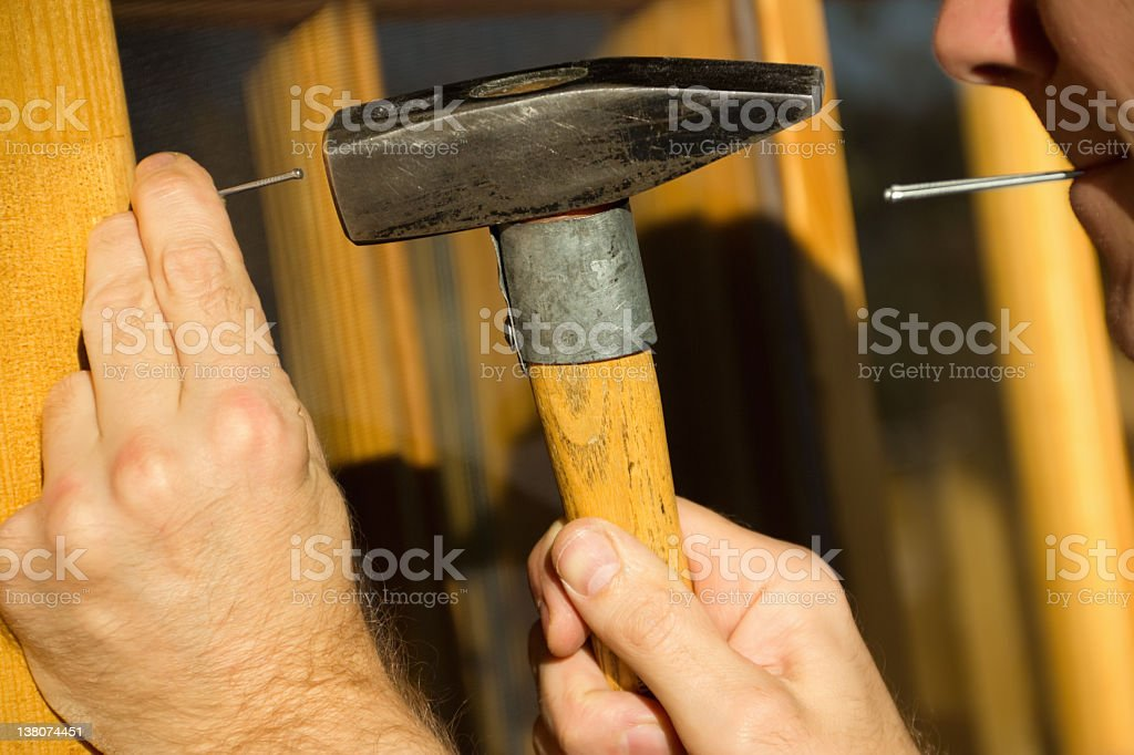 Man with a hammer to drive nails royalty-free stock photo