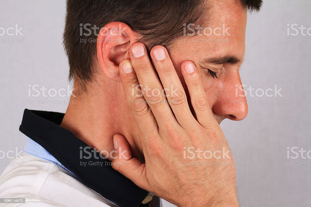 Man with a headache. Man with ear pain, Earache. stock photo