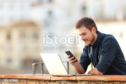 istock Man with a laptop checking phone content in a balcony 1083742996