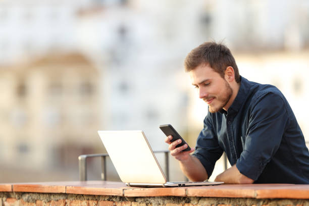 Man with a laptop checking phone content in a balcony stock photo