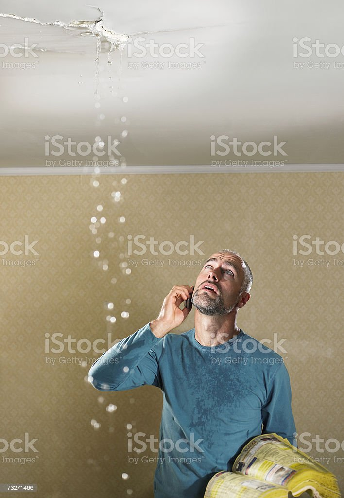 Man with a leaking ceiling using phone royalty-free stock photo