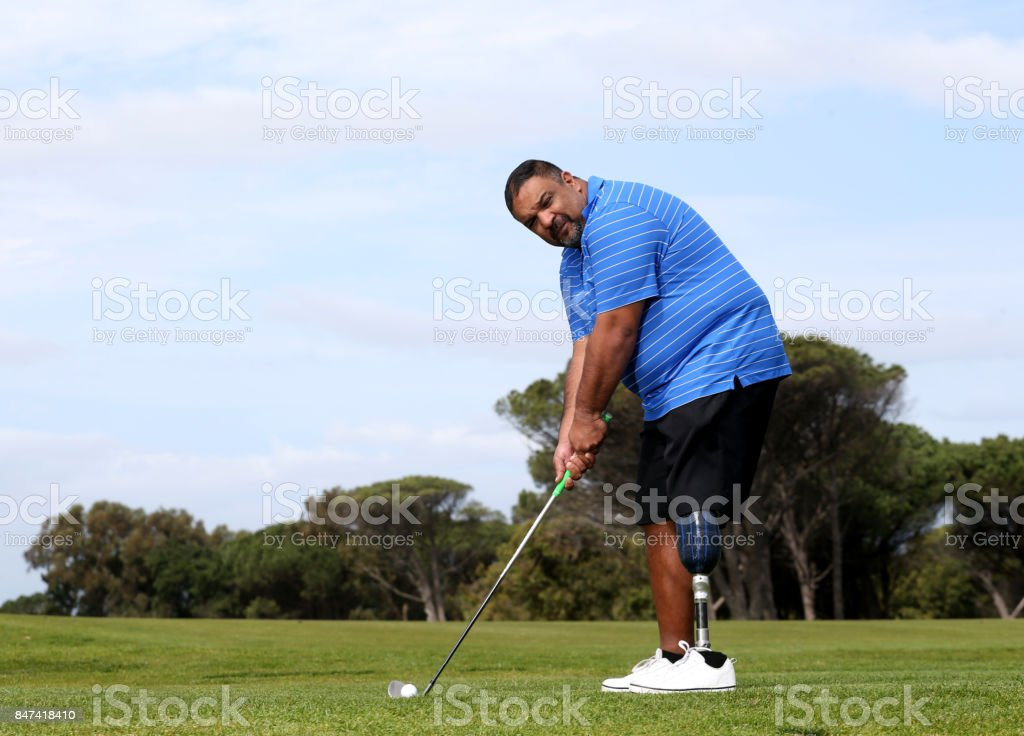 A man with a leg amputee playing golf stock photo
