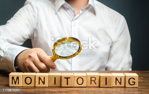 184640907istockphoto A man with a magnifying glass examines word Monitoring. Verification and control, business audit. Inspector controls the quality of products or work performance. Productivity enhancement, coordination 1170873201